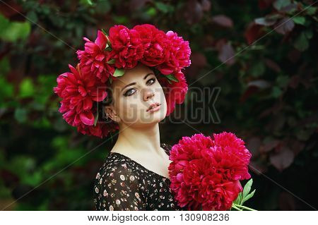 portrait of beautiful girl with red peonies