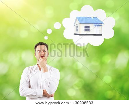 Mortgage concept with businessman thinking about house on green background