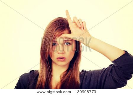 Teenage woman makes loser sign on her forehead