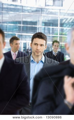Casul businessman walking in crowd in office lounge.