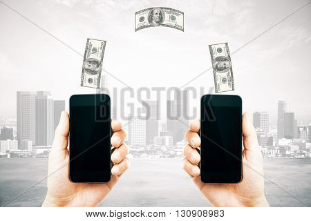 Online money transfer concept with two male hands holding smart phones with blank screens and dollar bills above on city background. Mock up 3D Rendering
