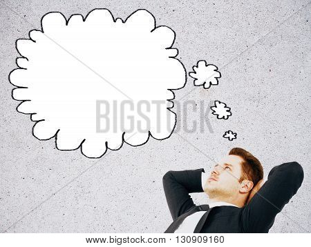 Relaxed businessman with thought cloud on concrete background. Mock up