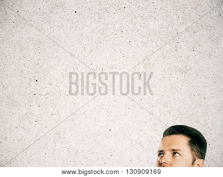 Half of businessman's head on blank concrete background. Mock up