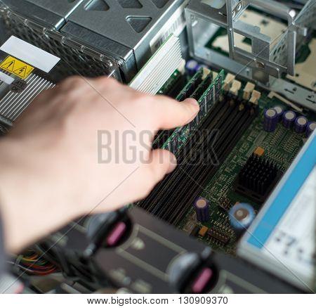 Computer Technician Installing Ram Memory Into Motherboard.