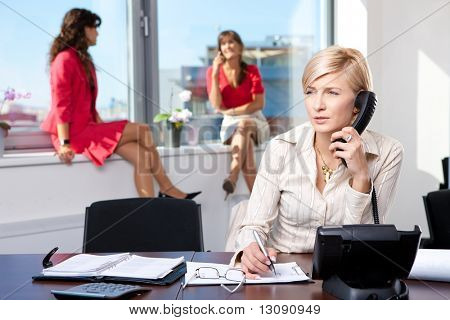 Young businesswoman sitting at desk in office, talking on landline phone, writing notes.