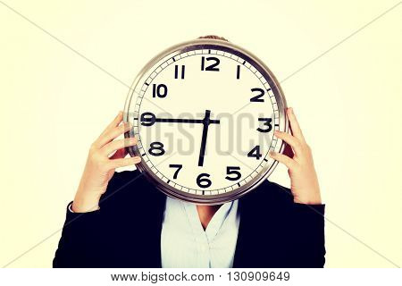 Business woman covering face with a clock