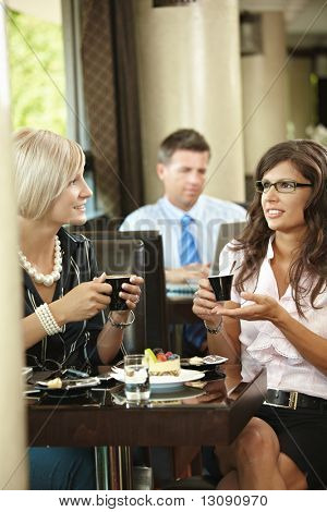 Businessman using laptop in cafe, young woman drinking coffee and talking in the foreground. Selective focus on women.