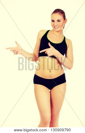Young athletic woman pointing for copyspace or something
