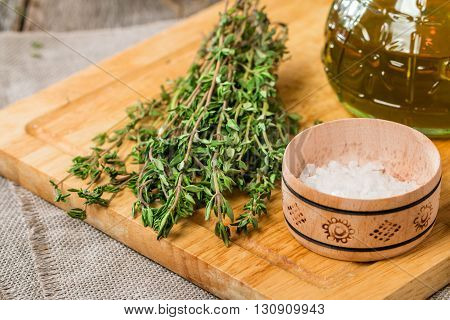 bunch of fresh organic thyme with salt on a wooden background