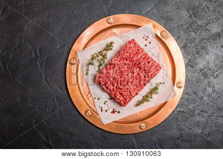 Minced meat on paper and copper metal tray with seasoning and fresh thyme on black background, top view