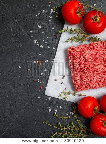Minced meat on paper with seasoning and fresh thyme on black background, top view