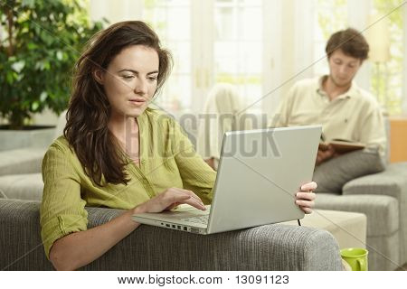 Couple at home. Woman using laptop computer, man reading book in background.
