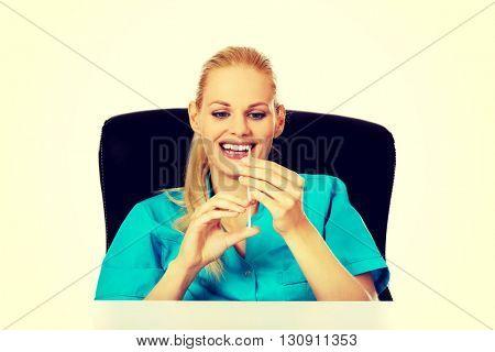 Funny female doctor or nurse sitting behind the desk and holding syringe