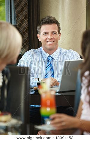 Portrait of happy businessman sitting at table in cafe, smiling.