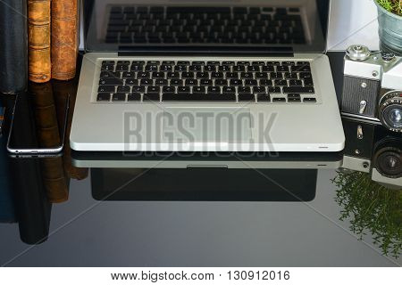 Laptop, flower and supplies with copy space on black glass desktop
