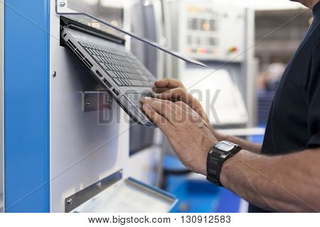 CNC machine. Operator working at programmable machine.