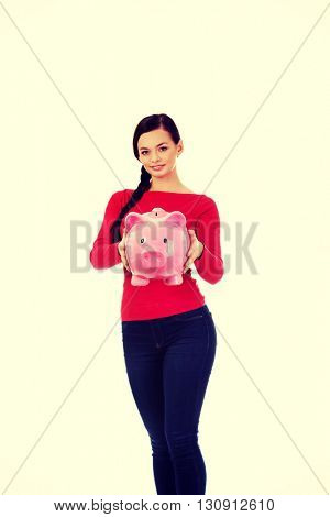 Happy young student woman holding piggybank