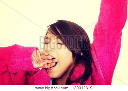 Beautiful yawning woman in pink bathrobe.