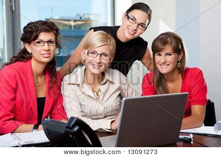 Team of  young businesswomen using laptop computer  in meeting room. Looking at camera, smiling.