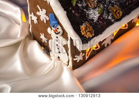 Christmas glazed gingerbread house with sugar snowman and walnuts on housetop. Against white silk background as a snow cover.