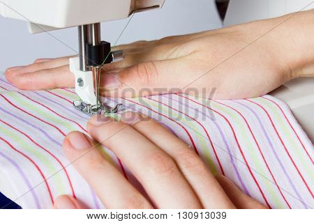 Foot of the sewing machine close-up on a striped cloth. Female hand seamstress in the garment sewing.