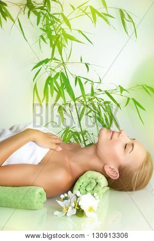 Beautiful calm girl with closed eyes relaxing on a massage table, medical therapy in a beauty salon, healthy lifestyle, woman enjoying day spa