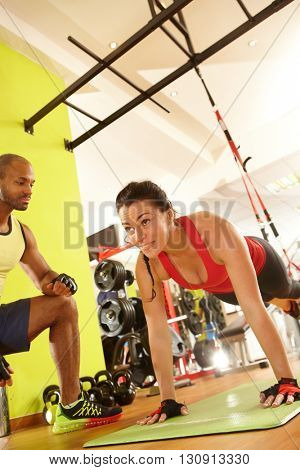 Woman doing suspension training with coach in gym.