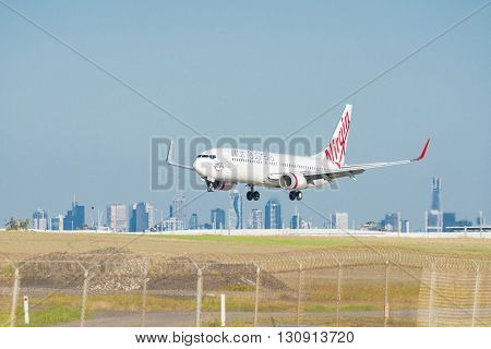 Melbourne, Australia - May 6, 2016: Close-up view of a Virgin Australia passenger airplane landing at Melbourne Airport, with CBD skyline in the background