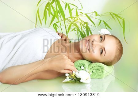 Portrait of a happy smiling woman lying down on a massage table at luxury spa salon, young female enjoying beauty treatment and pampering