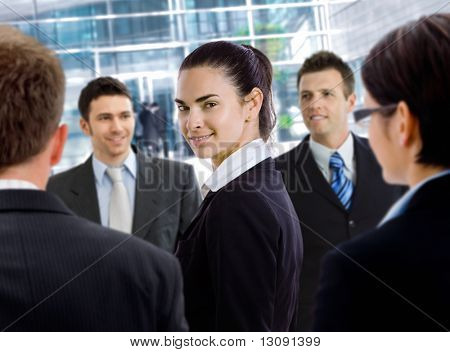 Young businesswoman standing among other businesspeople, in front of office building.