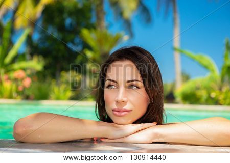 Portrait of a beautiful calm woman in a swimming pool, relaxing in a cold refreshing water on hot summer day, spending holidays on tropical beach resort, day spa