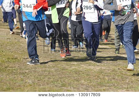Junior athletics runner on a cross country race. Outdoor circuit. Horizontal