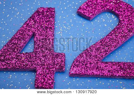 Number fortytwo purple color over a blue background. Anniversary. Horizontal