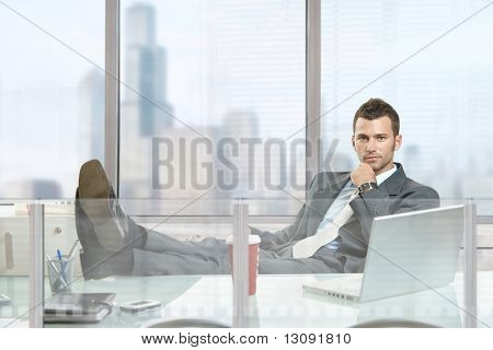Relaxed businessman sitting at desk in front of office windows, thinking.