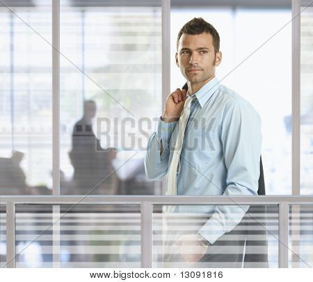 Casual businessman standing in front of glass walls in office, smiling.