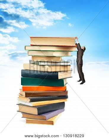 Businessman hanging on top of stack books blue sky background.