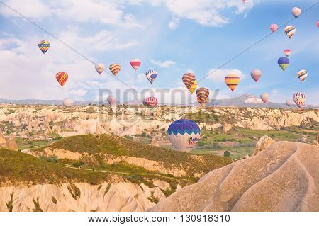 TURKEY GOREME - MAY 19 2015 - Multi-colored balloons fly over rocks.The greatest tourist attraction of Cappadocia the flight with the balloon
