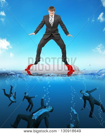 Businessman on lifebuoy with people drowning in sea