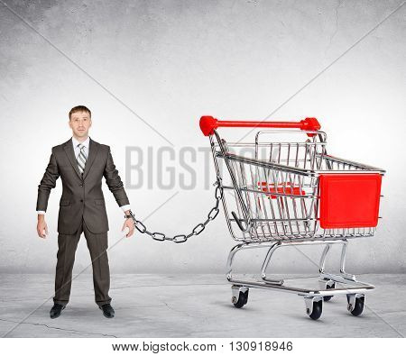 Businessman chained to shopping cart on grey background