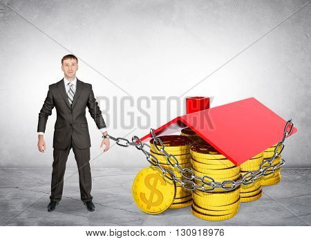 Businessman chained to house with coins on grey background