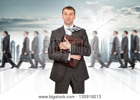 Businessman holding briefcase. Many people walking on background