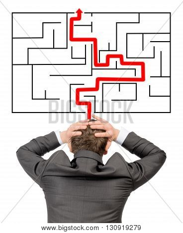 Confused businessman in front of labyrinth with red line showing the way out