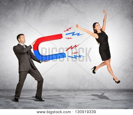 Concept of capturing people with marketing. Businessman attracting woman with magnet