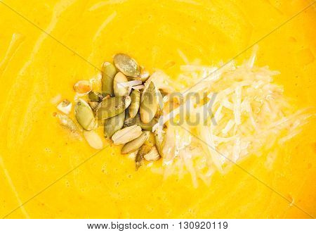 Pumpkin cream soup with grated cheese and seeds. Macro. Photo can be used as a whole background.