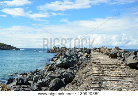 Wooden track extending out onto a harbor breakwater