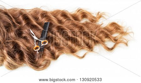 The strands of curly hair, comb and scissors isolated on white background.