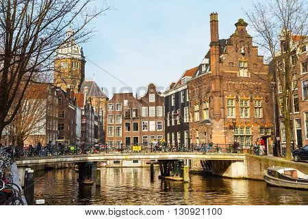 Amsterdam, Netherlands - April 2, 2016: Traditional old buildings, church, canal and bridge view with bicycles in Amsterdam, the Netherlands