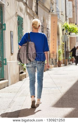 Woman walking on old traditional cobbled street in old coastal town of Piran in Slovenia, Europe.