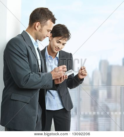 Two businesspeople standing on balcony of downtown office building, using smart mobile phone, smiling.