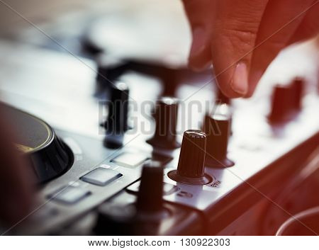 Dj playing music on modern midi controller turntable. New audio technology for mixing tracks in digital format. Shallow depth of field unrecognizable male model.